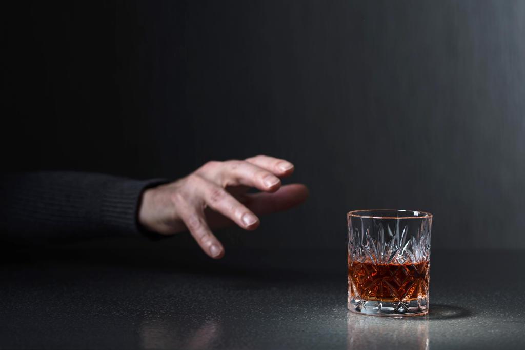 Imagen oscura en la que se ven un vaso con una bebida alcohólica y una mano que trata de alcanzar el vaso
