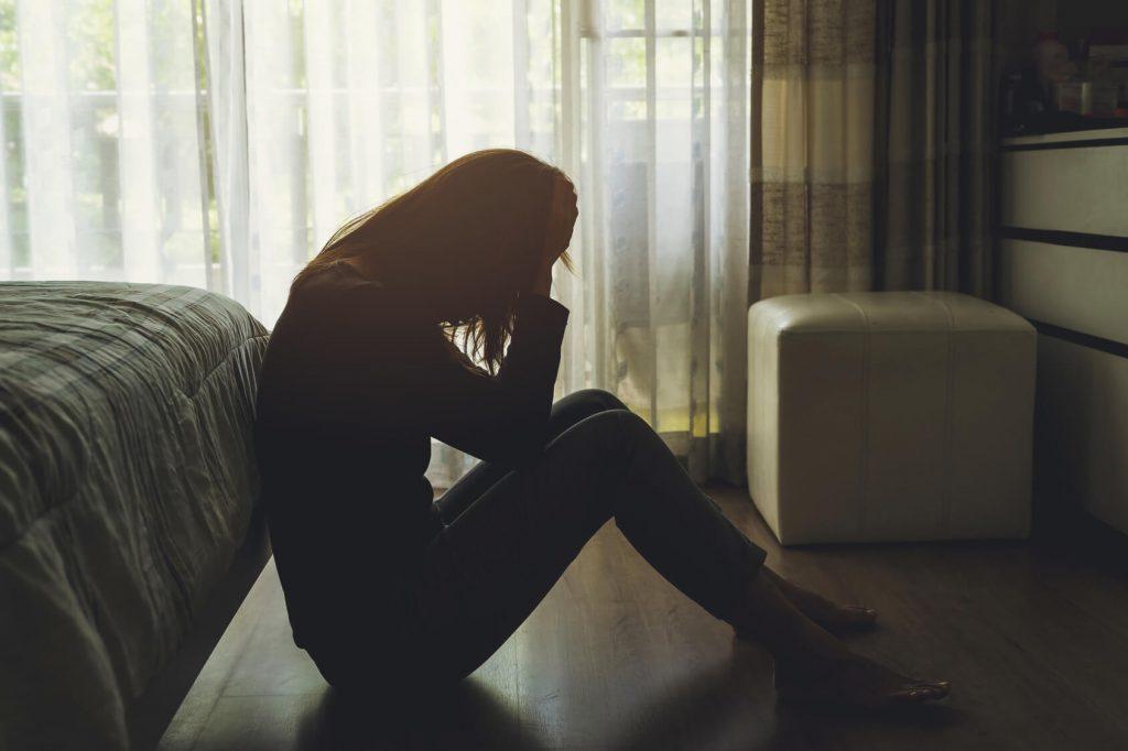 Mujer depresiva sentada en el suelo de una habitación a oscuras apoyada en la cama
