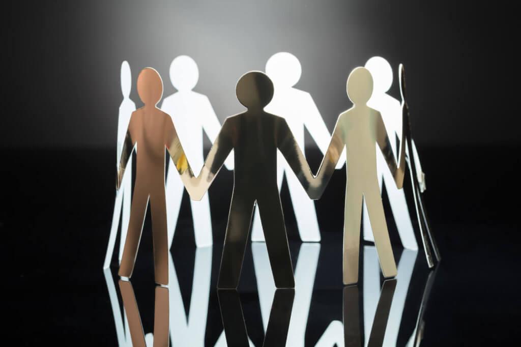 Imagen que refleja unos monigotes cortados en papel que hacen un círculo dándose las manos