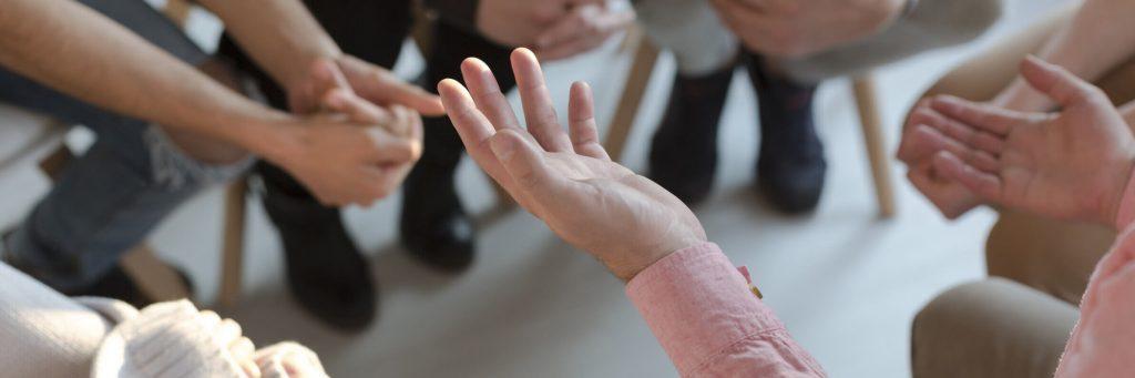 Imagen en la que se ven las manos y los pies de un grupo de personas sentadas en círculo