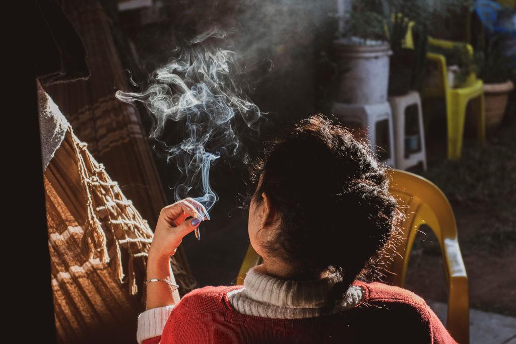 Una chica de espaldas fuma una sustancia estupefacientes