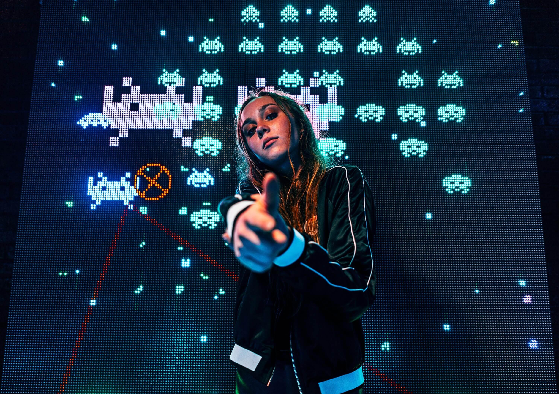 Una chica con la posición de empuñar un arma y detrás una pantalla con juegos de arcade