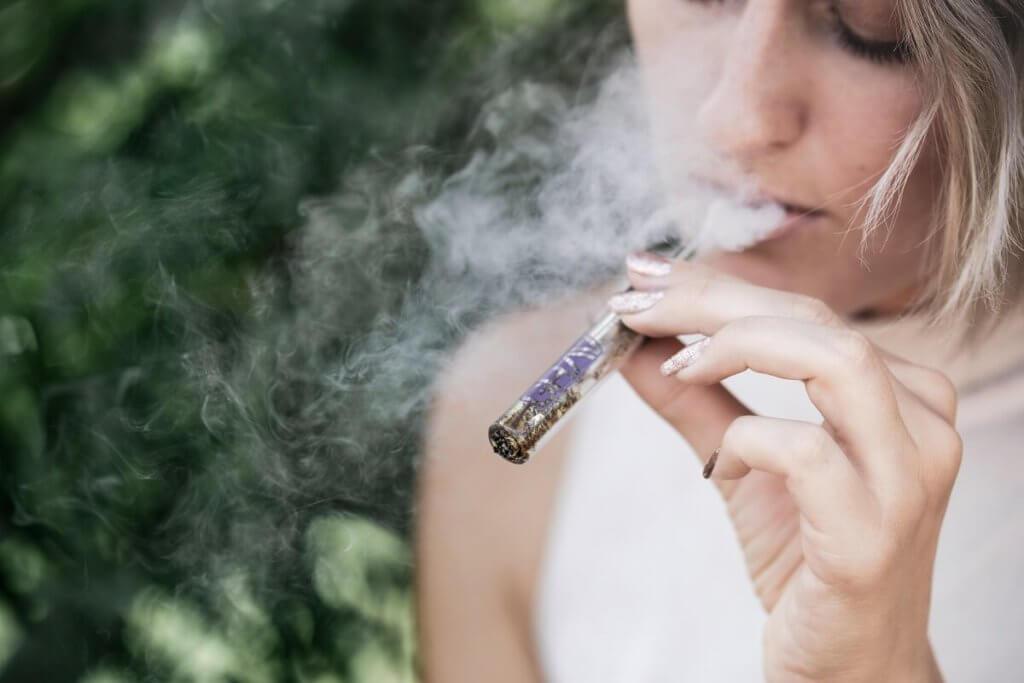 una chica jóven fuma de un vapeador