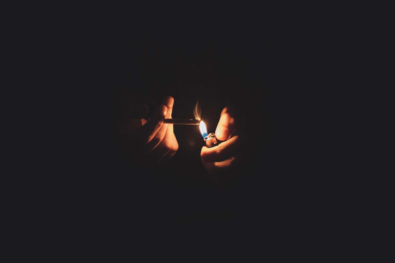 Imagen de unas manos encendiendo un cigarro, todo a oscuras, solo se ven las manos, la llama y el mechero