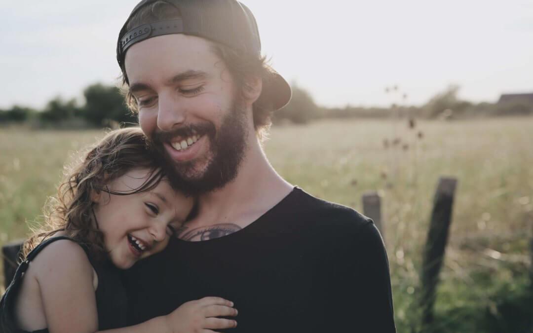 Se ve a un padre que coge a su hija pequeña en brazos, ambos sonríen