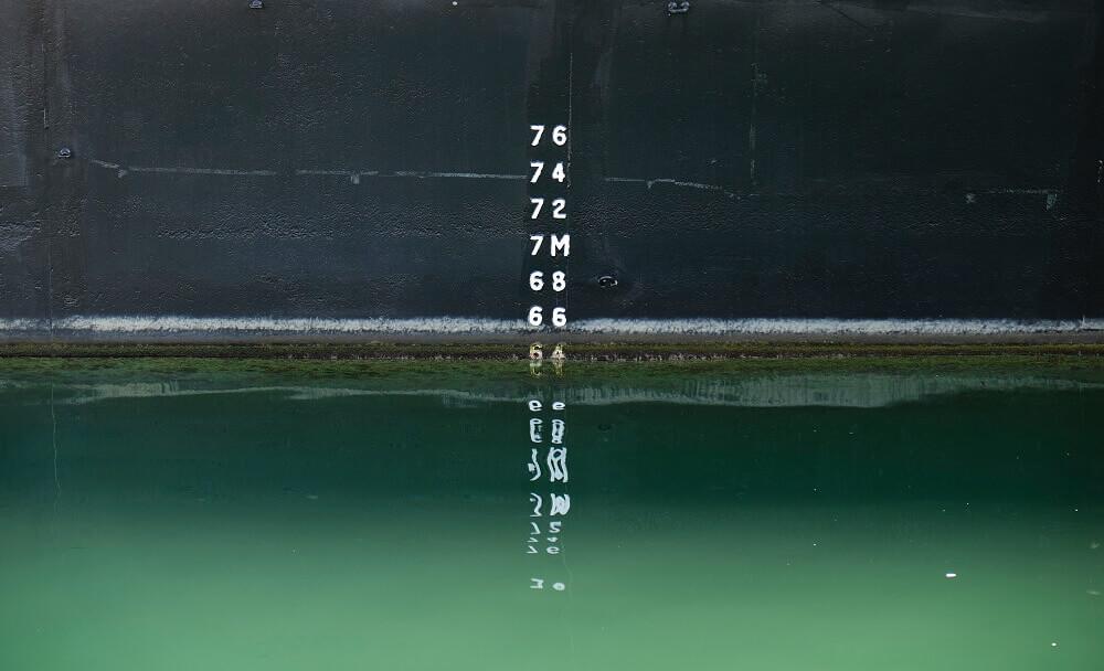 Imagen en la que se ve un medidor de líquido sobre una pared, como una presa, una piscina