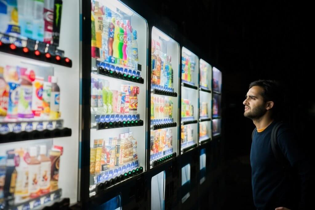 Un chico mira atentamente unas neveras llenas de bebidas energéticas