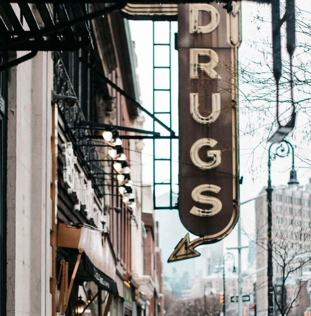 Una señal en la que pone drugs y apunta hacia una puerta