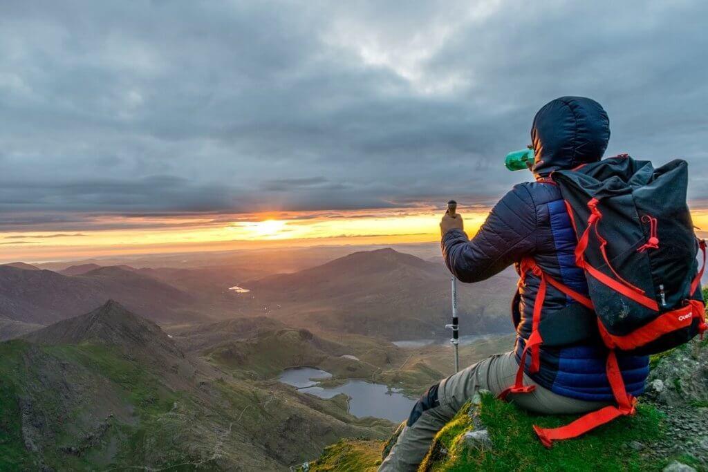 Una persona encima de una montaña ingiriendo una bebida energética