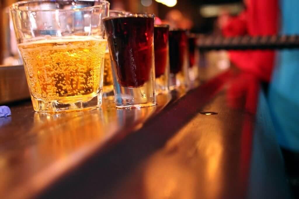 Imagen de una barra de bar en la que se ven combinados de alcohol y bebidas energéticas