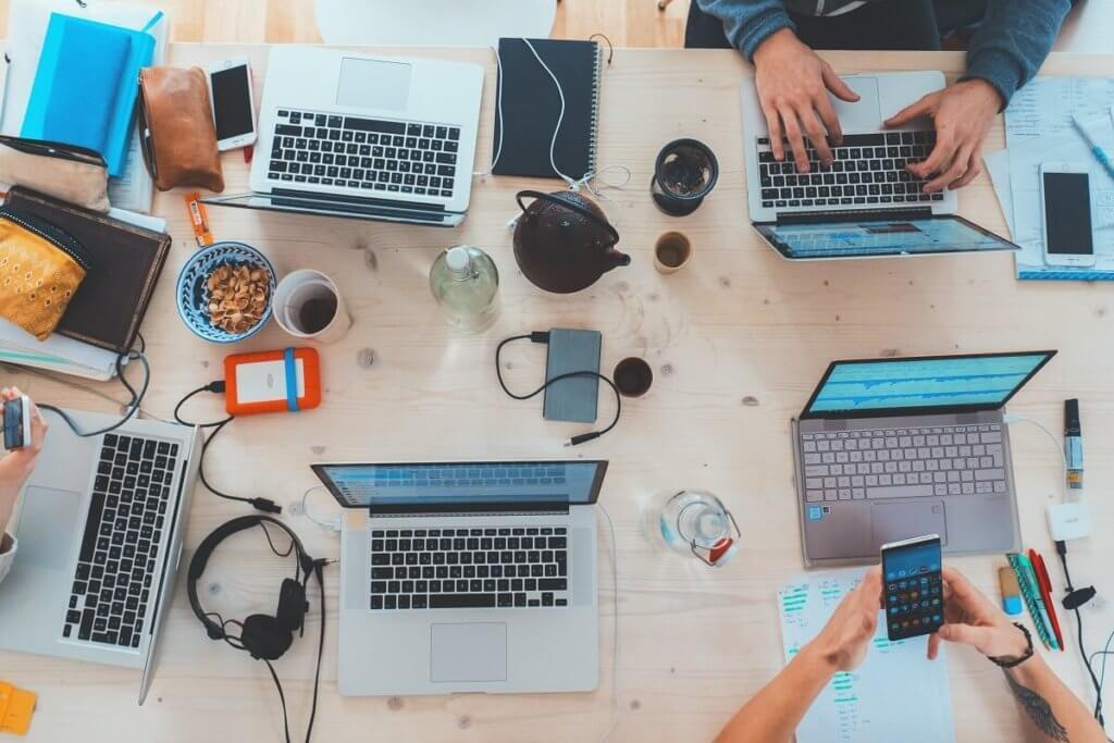 Mesa de oficina vista desde arriba llena de ordenadores, teléfonos y gente trabajando