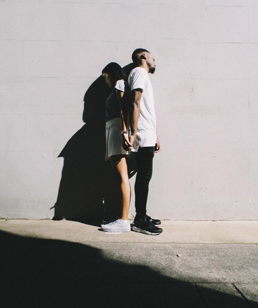 Una pareja de agarran las manos pero se dan la espalda, uno de ellos al sol, la otra en la sombra