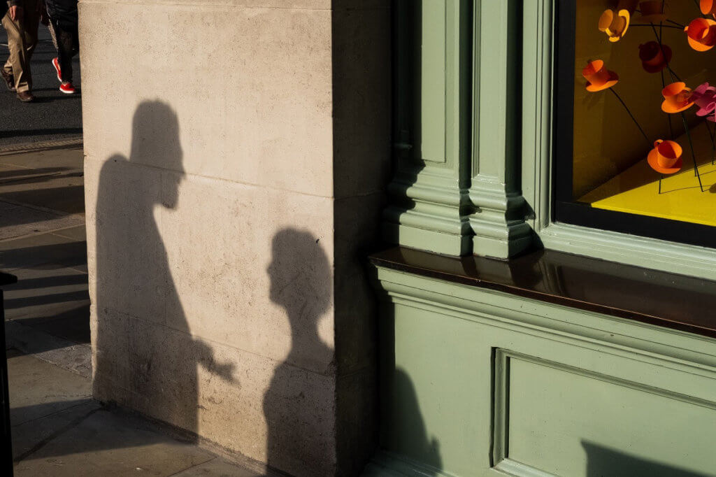 En la sombra de la pared se ve como a dos personas discutiendo