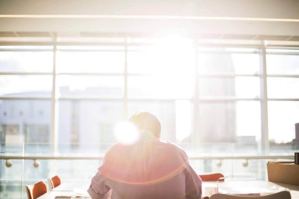 Imagen de espaldas de un hombre sentado en una mesa de trabajo