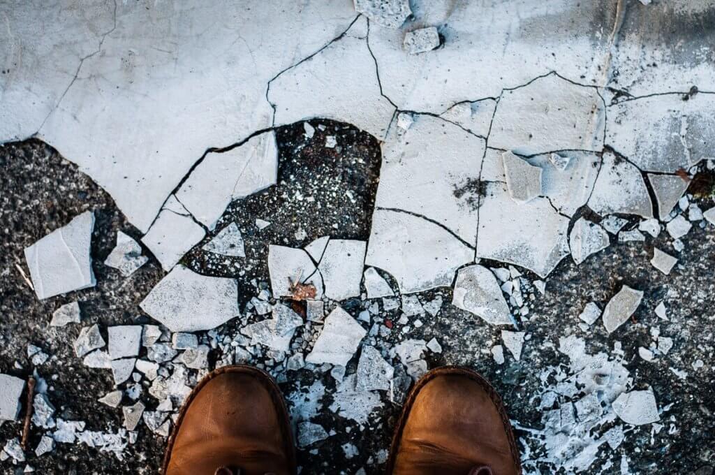 Imagen de unas botas que pisan un suelo helado resquebrajado
