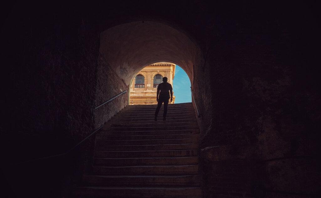 Imagen de un chico que sube unas escaleras y al final se ve un arco con luz