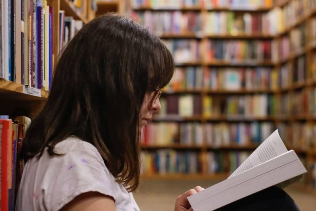 Una chica lee un libro en una biblioteca