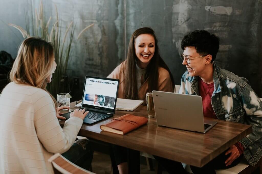 Grupo de estudiantes con sus ordenadores en torno a una mesa
