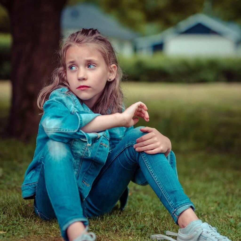 Una niña con cara y actitud tristes mira hacia la lejanía