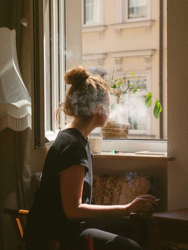 Una chica fuma un cigarro mirando por la ventana