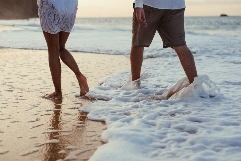 Pareja camina por la orilla del mar