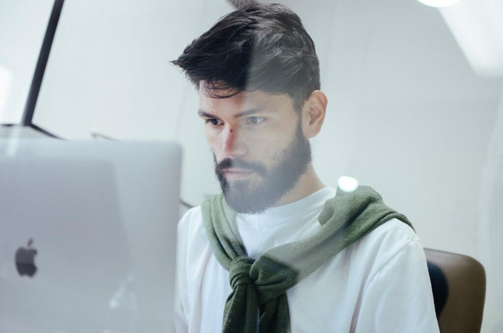 Se ve a un chico trabajando con el ordenador, muy concentrado