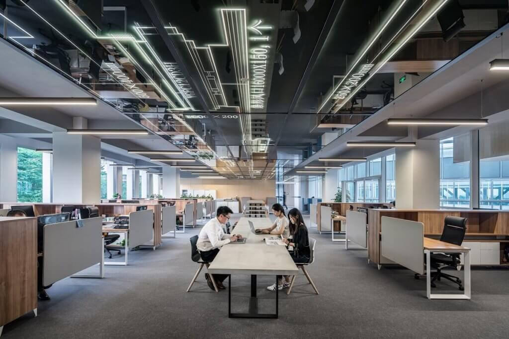 Imagen de una oficina enorme en la que se ve a tres personas trabajando en el centro