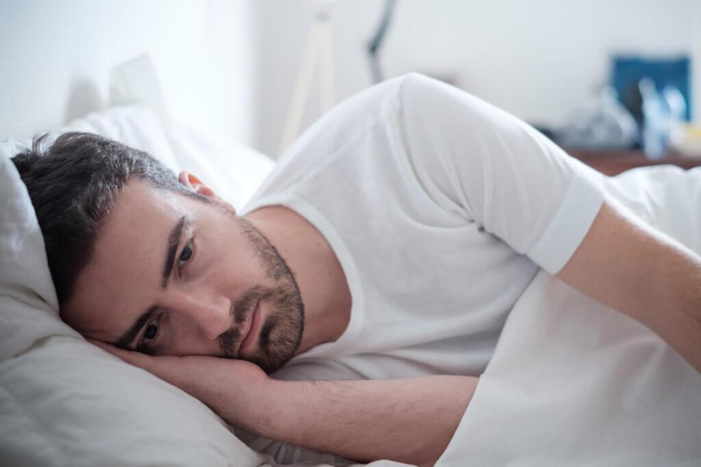 Un chico con actitud depresiva está tumbado en al cama con la mirada perdida