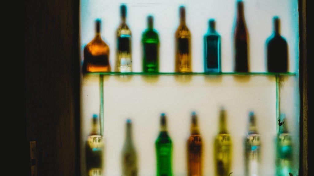 Imagen de una estantería donde se ven muchas botellas de alcohol borrosas