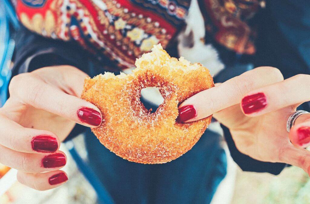 Imagen de una chica sosteniendo una rosquilla en las manos a medio comer. Alimentos adictivos con alto contenido en grasas, azúcares, etc.