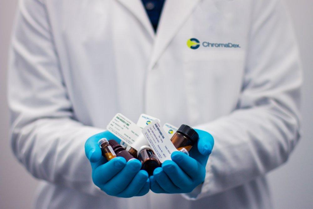 Foto de un médico con botes de pastillas en las manos