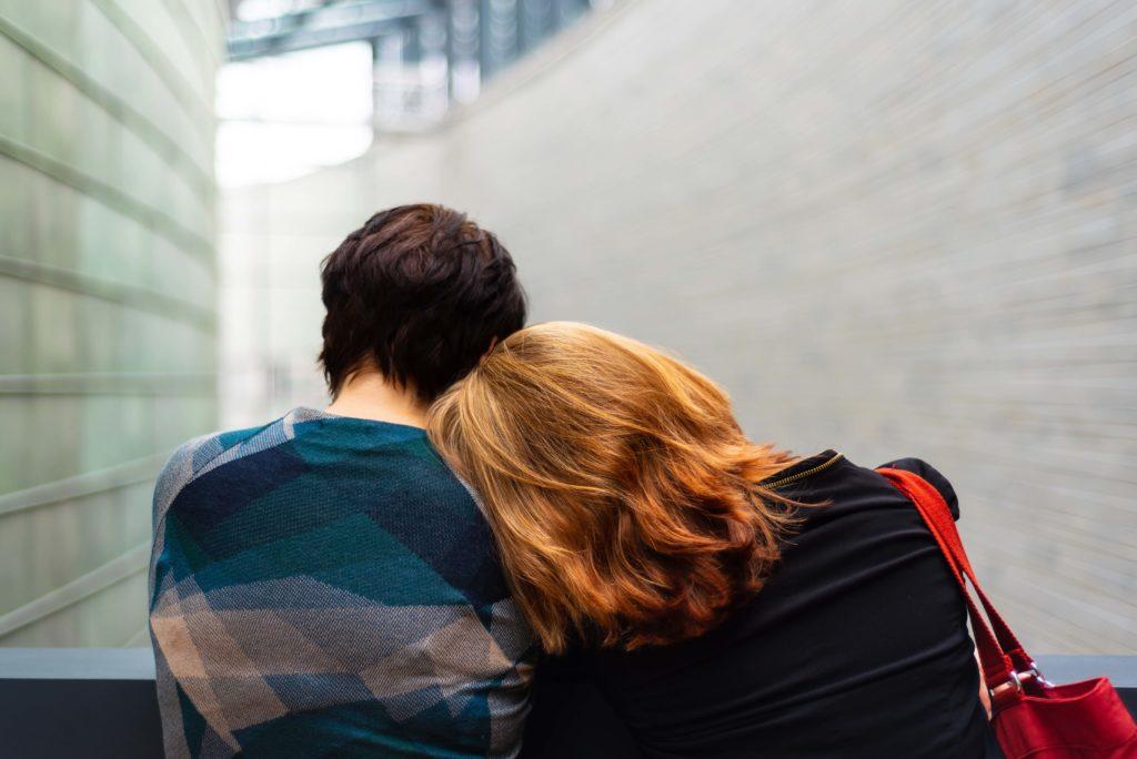 una pareja vista de espaldas, sentados en un banco, una de ellas apoya su cabeza sobre el hombro de la otra persona