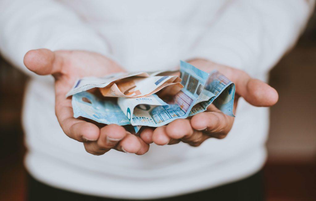 manos con billetes de veinte y cincuenta euros