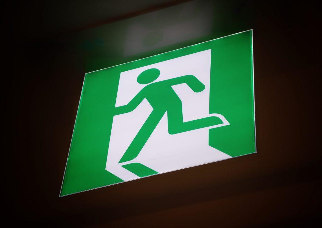 señal de salida, fonde verde, monigote blanco saliendo por una puerta