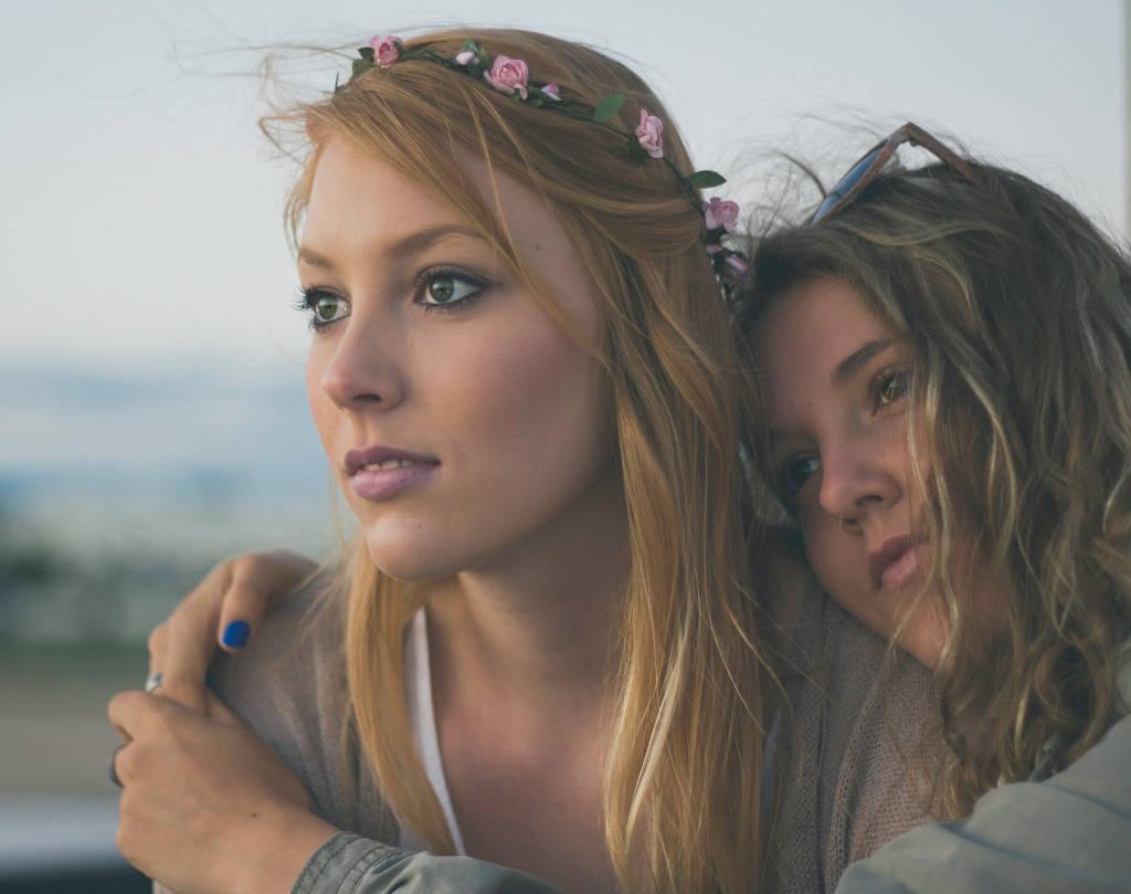 dos mujeres abrazadas mirando hacia adelante