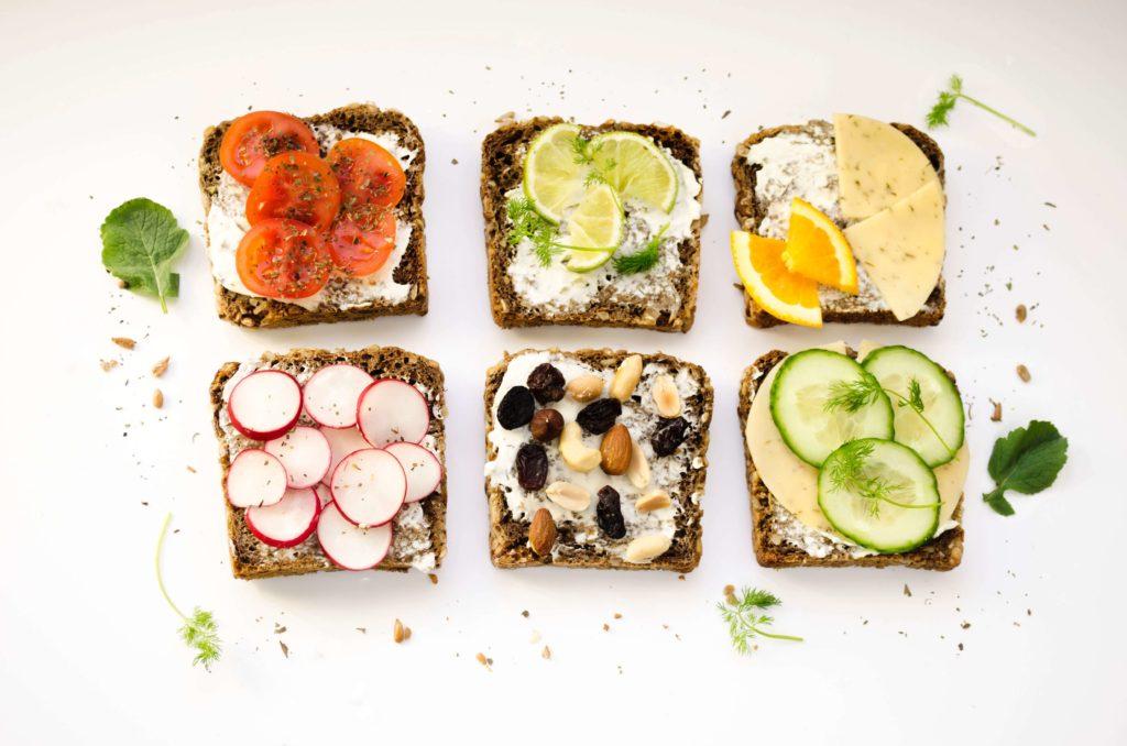 alimentacion saludable imagen de varias tostadas saludables vistas desde arriba con tomate, pepino, frutos secas, nabo