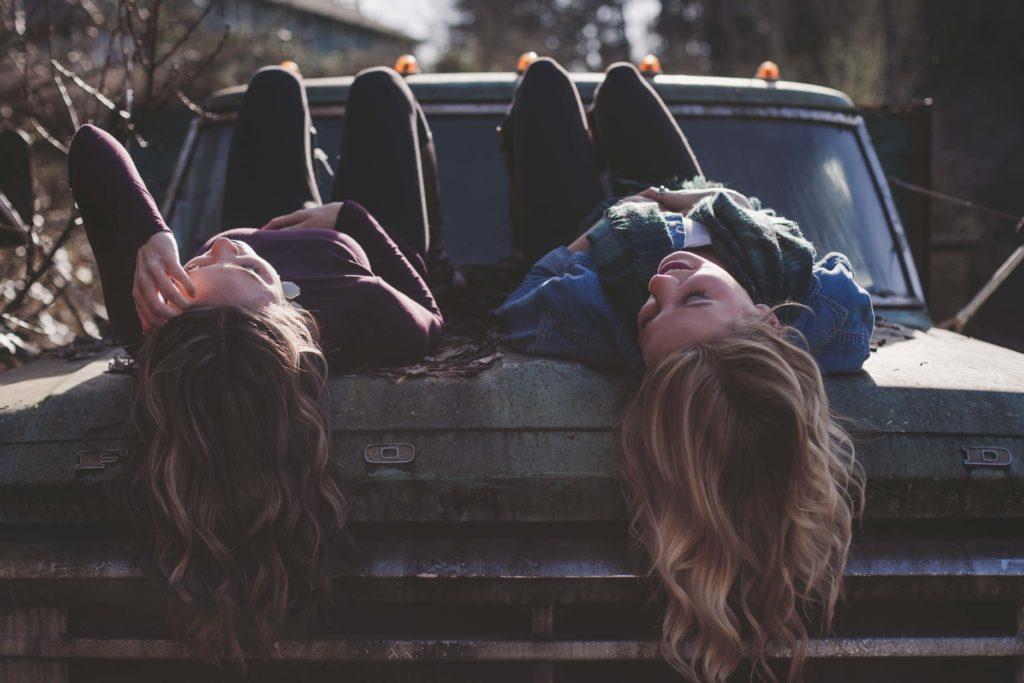 dos chicas tumbadas en el maletero de un coche se miran y sonrien de forma complice