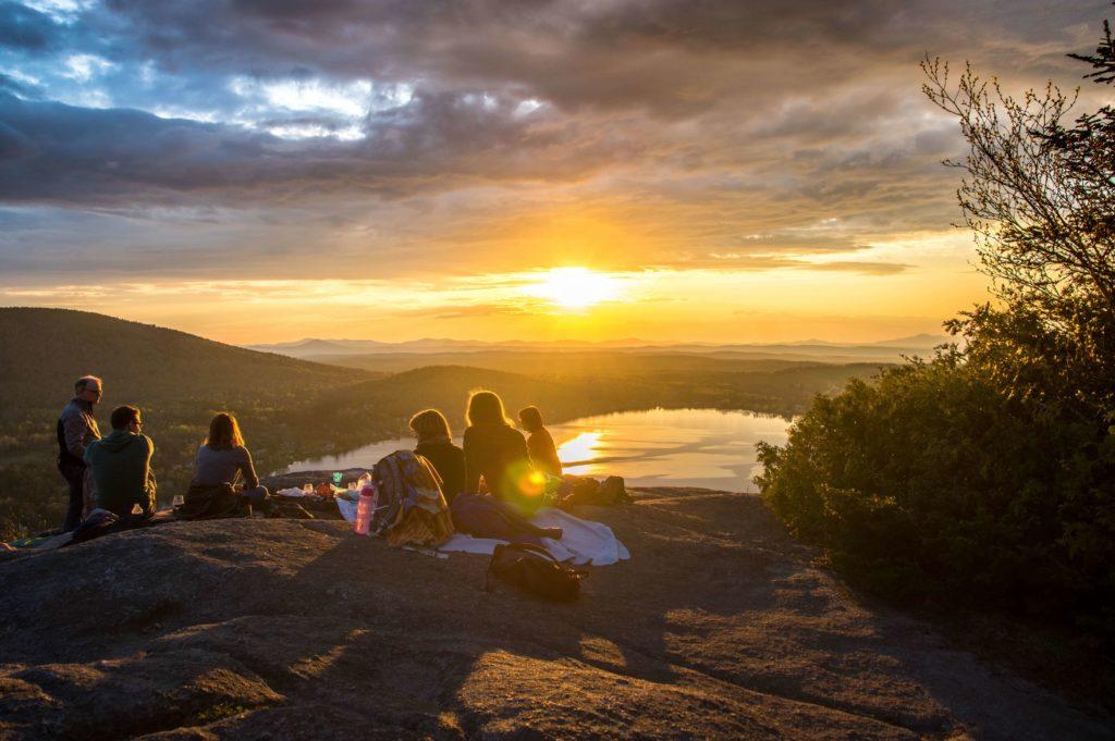 grupo de gente sentados en el campo viendo una puesta de sol
